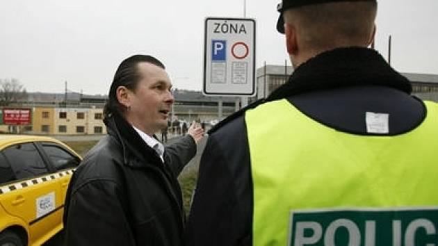 Mluvčí nespokojených taxikářů Zdeněk Ponert ukazuje značku, která jim znemožňuje vjezd na parkoviště u holešovického nádraží.
