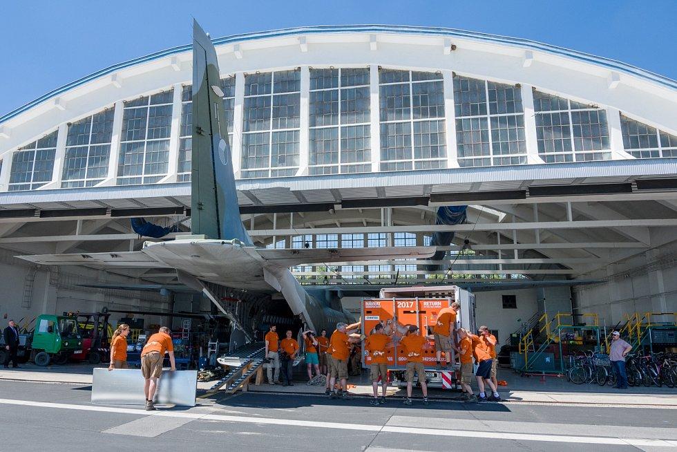 Nakládání transportních beden s koňmi do letounu CASA na letišti ve Kbelích.