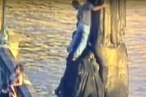 Cizinci lezou na sochu z Karlova mostu.