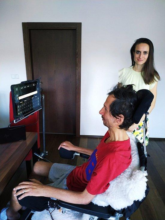"""Vladimír Mikulášek komunikuje s manželkou Denisou prostřednictvím tabletu a zařízení Tobii. Tobii snímá pohyb očí, které Vláďa upírá na klávesnici. A tablet pomocí hlasového výstupu čte, co Vláďa pomocí očí """"vyťuká"""" na tabletu"""