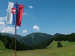 Slovenská vlajka. V pozadí je pohoří Malá Fatra.