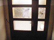 Poničená skleněná výplň dveří v ulici 5. května.