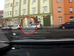 Muž skákající po autě.