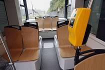 Zadní část tramvaje a dřevěné sedačky.
