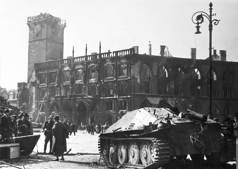 Povstalci zničili mnoho obrněných vozidel, včetně tohoto stíhače tanků Hetzer. V pozadí jde vidět vyhořelá staroměstská radnice.