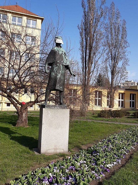 V parku u ZŠ Jeseniova nosí v době koronavirové epidemie i socha.