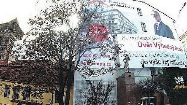 Z POHLEDU od nábřeží je štítová zeď domu jednou velkou reklamní plochou. Spolu s barokním domečkem a vodárenskou věží v těsném sousedství poskytuje nekompaktní podívanou.