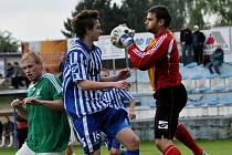 Vltavínský gólman Ladislav Čaba stahuje míč před domácím útočníkem Tomášem Hajduškem.