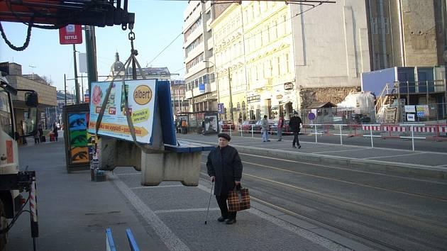 Dělníci odstraňují jednu z 250 laviček společnosti AD-Net. Obyvatelé Prahy 8 to nepotěšilo.