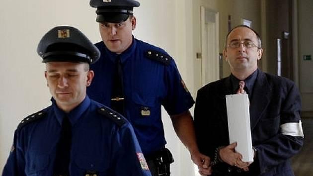 Obžalovaný Mikuš (zcela vpravo) přichází za doprovodu policejní eskorty do soudní síně.