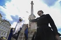 """Darina Alster (vlevo) při happeningu a vztyčení praporu """"nebinární"""" Madony, 2. září 2020 u mariánského sloupu na Staroměstském náměstí v Praze."""