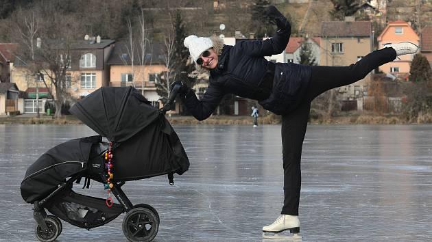 Ledová Praha - zamrzlý Kyjský rybník. Lidé si přes něj zkracují cestu na vlak, maminky bruslí s kočárkem a hraje se tu hokej.