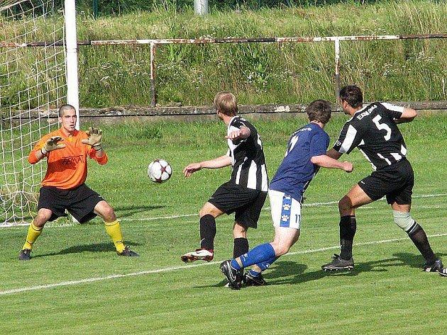 PLNÉ NASAZENÍ. Fotbalisté Radotína (v černobílém) v ostrém vstupu do sezony obstáli.