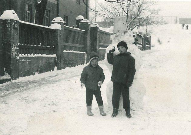 Vykáňská. Helena Černá (vlevo) s Pepíkem Šindelářem v roce 1970. V klidné části Nových Strašnic se mohly děti dosyta vyblbnout, nehrozilo jim žádné nebezpečí ani uprostřed silnice. Vzadu na fotce lyžují děti z  kopce pod sportovním hřištěm.