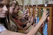 Z výstavy dřevěných reliéfních obrázků světců a patronů s jejich atributy v historickém mázhausu v přízemí Novoměstské radnice v Praze.
