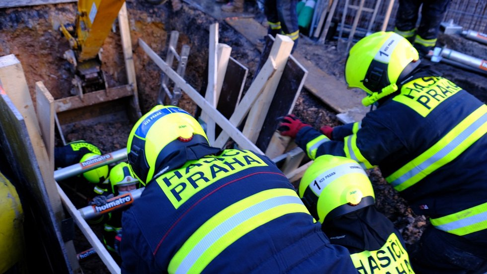Pražští hasiči se snaží vyprostit dělníka, jehož na Smcíhově zavalila zemina.