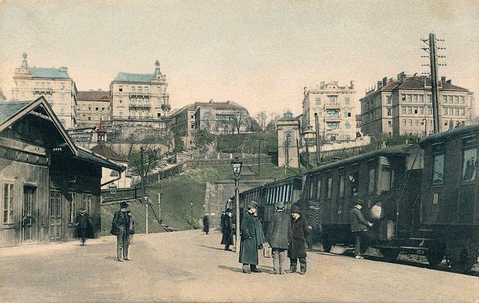 Původní staniční hrázděná budova Královských Vinohrad se nacházela mezi oběma tratěmi a ke krátkým nástupištím vedl nadchod.