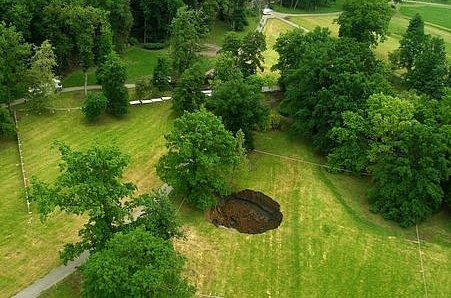 Letecký pohled na dvacetimetrový kráter vzniklý při hloubení tunelu Blanka vedoucí zčásti pod pražskou Stromovkou.