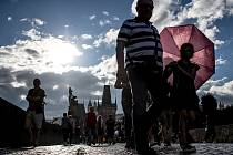 Lidé procházejí 12. července po Karlově mostě v Praze.