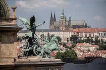 Pohled na trigy na budově Národního divadla a v pozadí Pražský hrad 25. května v Praze.