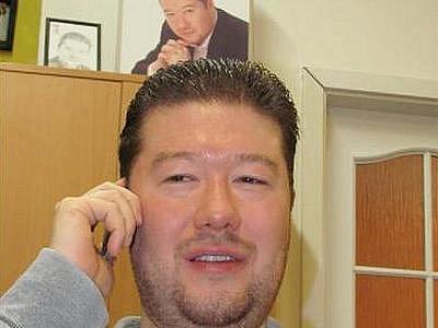 Tomio Okamura ve své kanceláři, na pozadí titulní strana jeho první knihy.