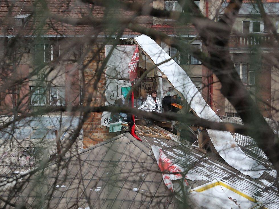 Squatteři nerespektují vývzu soudního exekutora a zůstávají i po vyklizení Kliniky na pražském Žižkově na střeše budovy.