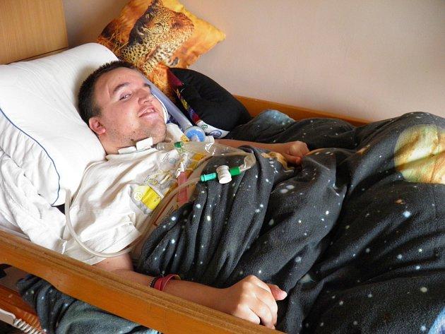Pětadvacetiletý Tomáš Janoušek z Ďáblic už je téměř sedmnáct let upoután na lůžko. Díky péči své maminky nemusí být trvale v nemocnici. Do Motola dojíždí pouze jednou za tři týdny, kdy mu mění kanylu trubici, pomocí které Tomáš dýchá.
