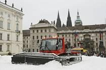 Rolba před branou Pražského hradu upravuje terén pro pořádání běžeckých závodů Pražská lyže.