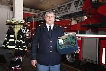 Vedoucí IZS a služeb krajského ředitelství HZS Středočeského kraje Petr Chalupník s oceněním vedle hasičské techniky na základně v Kladně.