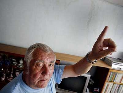 Pan Říha sedí před zničenou zdí svého bytu v panelovém domě letňanského sídliště.