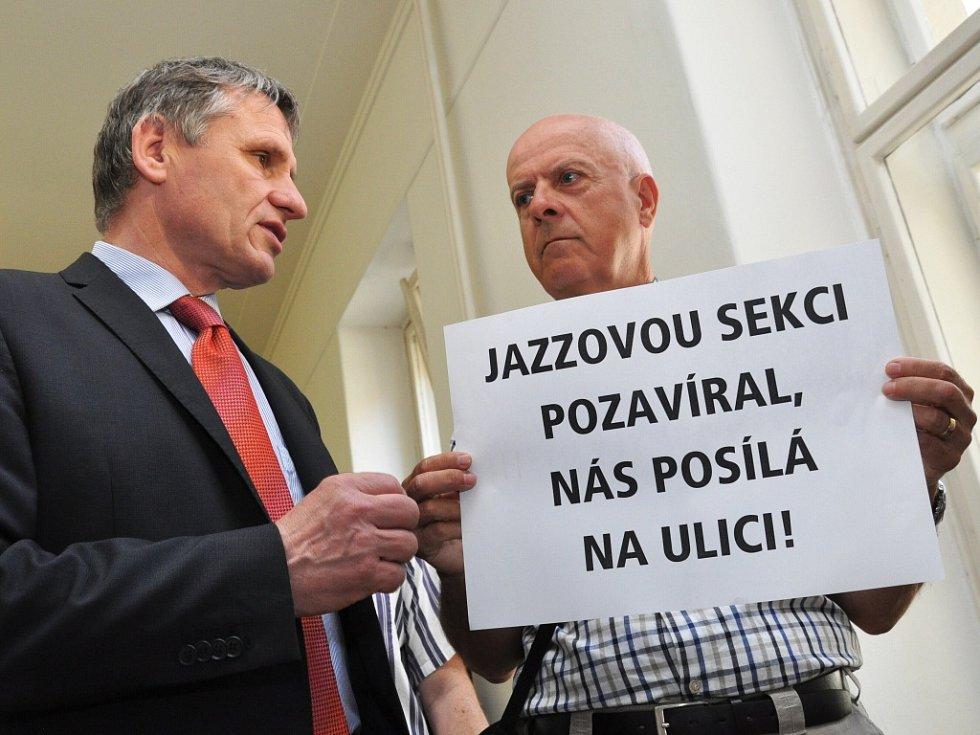 Desítky občanů s hesly v rukou přišly sledovat jednání přímo k soudu; před dveřmi jednací síně je ale na pokyn justiční stráže lidé museli odložit. Vlevo senátor Jiří Čunek.