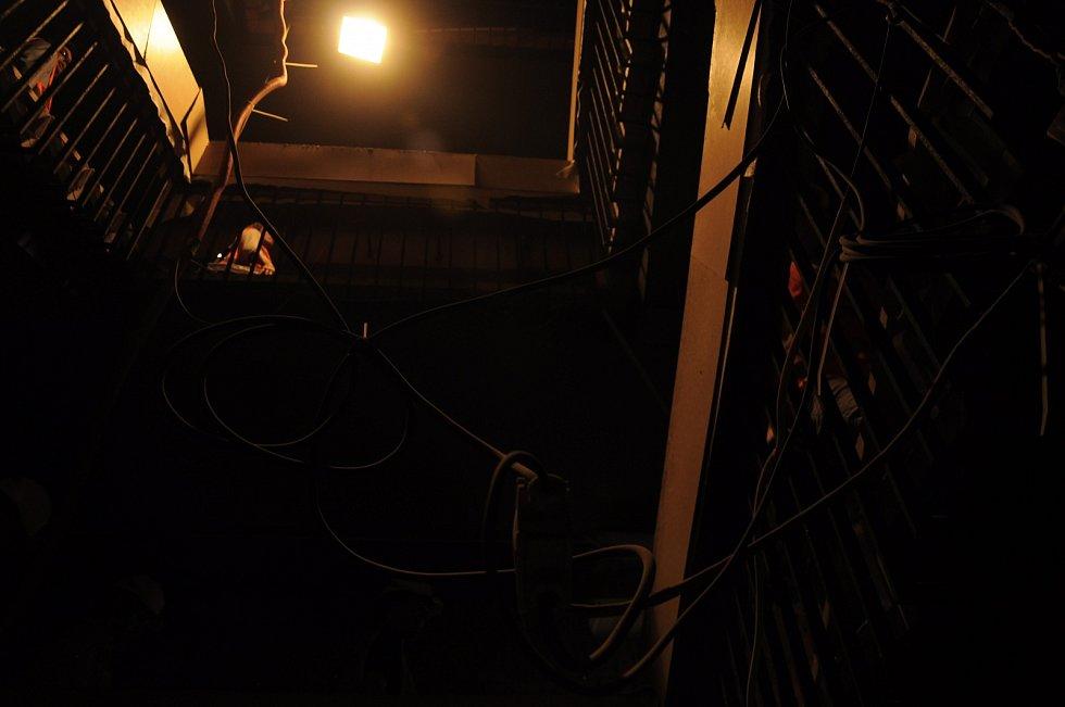 Schodiště je chráněno kartonem, všude visí kabely.