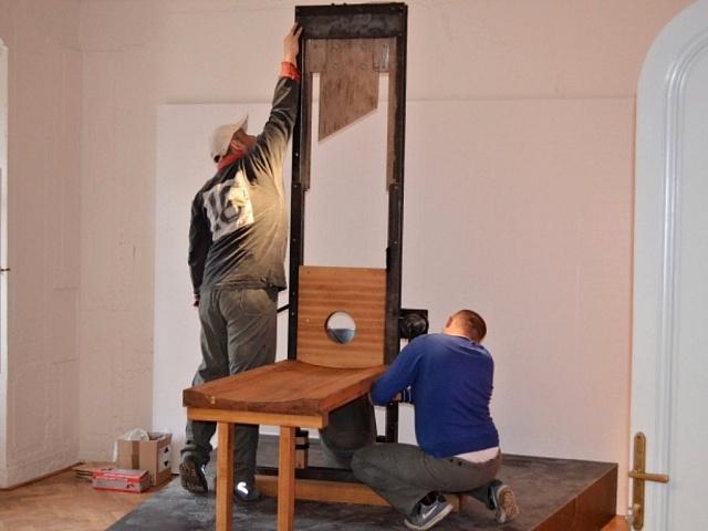Vězni vyrábějí gilotinu.