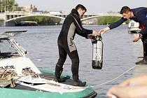 MÍSTO SRÁŽKY. Zasahující policejní potápěči se pokoušejí lokalizovat a vyzvednout potopený člun.