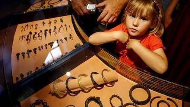Malá návštěvnice si prohlíží část expozice šperků.