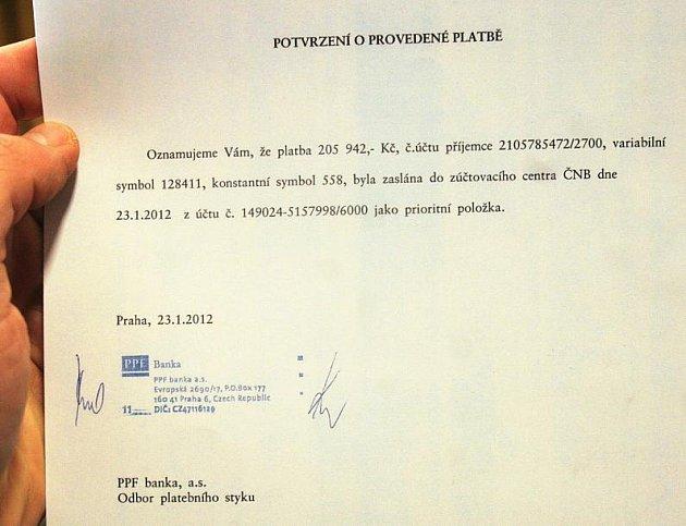 Primátor Bohuslav Svoboda ukazuje potvrzení o provedené platbě ohledně exekuce na majetek Prahy.