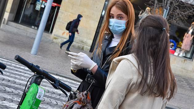 Prázdné ulice Prahy a lidé s rouškami 18. března 2020. Slečny se snaží aktivovat koloběžku, Václavské náměstí.