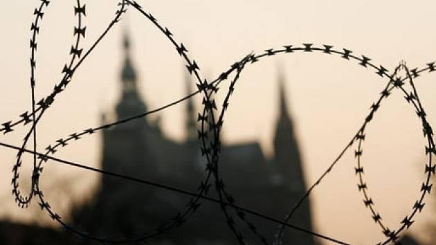 Pohled na Pražský hrad a věže svatovítské katedrály přes ostnatý drát.