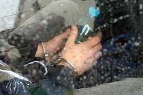 Zadržený muž v poutech. Ilustrační foto.