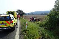 ZAKLÍNĚNÁ V AUTĚ. Řidička po nehodě, kdy skončila v poli na střeše, zůstala zaklíněná v autě. Na pomoc ji museli přijet hasiči.