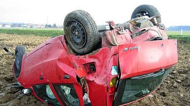 Po havárii skončilo vozidlo na střeše v poli.