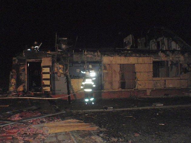 Požár zachvátil přízemí zničeného objektu a ve větru hrozilo další rozšíření do okolí.