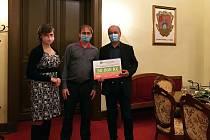 Petra Harabišová z odboru životního prostředí a starosta Frenštátu pod Radhoštěm Miroslav Halatin (vpravo) převzali od Ivo Valového z odboru životního prostředí krajského úřadu pomyslný šek na 50 tisíc korun za vítězství v Baterkománii.