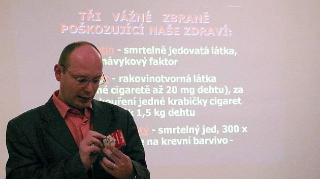 Lukáš Jureček ukazuje, kde na krabičce musí být uvedeno množství tří škodlivin – nikotinu, dehtu a oxidu uhelnatého.