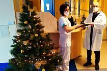 Vrchní sestra neurologického oddělení Alžběta Šimáčková přebírá symbolické vánoční poselství od kaplana Mgr. Boka.