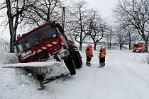 Dvě jednotky hasičů zasahovaly ve čtvrtek před polednem v obci Tísek, kde skončil pravou stranou v příkopu těžký dvaadvacetitunový sypač s nákladem kameniva.
