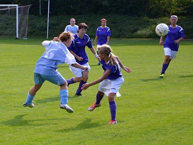 Štramberská fotbalistka Vajdová (vlevo) odvrací hlavičkou míč před dvojicí stachovických hráček.
