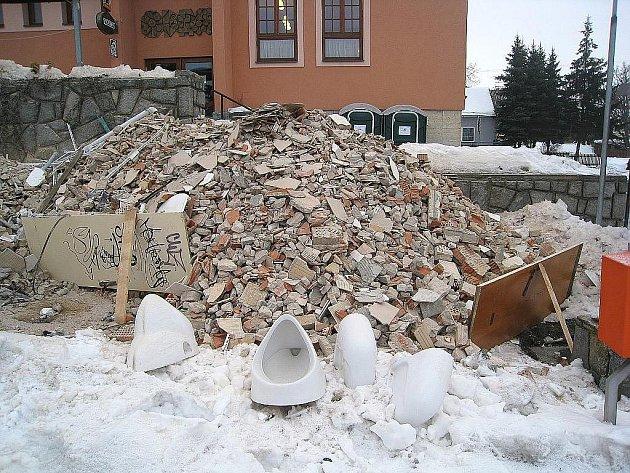 Hromada stavebního odpadu před provizorními WC u Dělnického domu v Odrách.