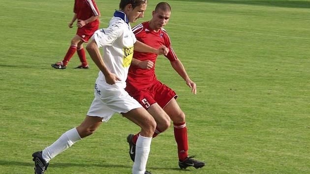 Útočník Jiří Beneš z Lichnova (v bílém) nastoupil proti hráčům Pusté Polomi (v tmavém) s kapitánskou páskou.