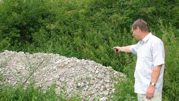Zdeněk Hrivňák ukazuje na hromadu stavebního odpadu, který údajně již delší dobu naváží na obecní pozemek  štramberský zastupitel Michal Dostál.